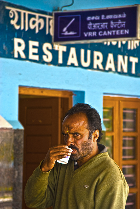 The quaint railway station of this town has vibrant blue colored walls with hand painted signage. This man became quite self conscious once he noticed I was aiming the camera at him. Thankfully a few seconds after this capture.