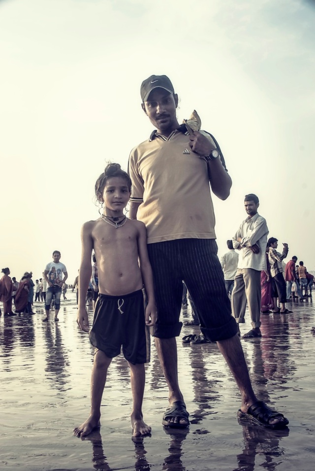 On a day off, a Sikh father takes his son for a swim on the beach whilst celebrating the Ganpati festival on Juhu beach in Mumbai